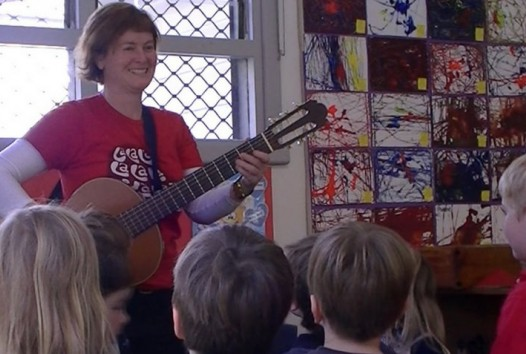 woman playing guitar to children