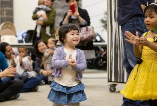 children clapping and laughing at performance