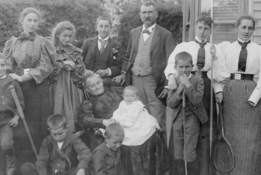 Group of women, children, grandmother nursing baby and a man, all whole-length, standing and sitting