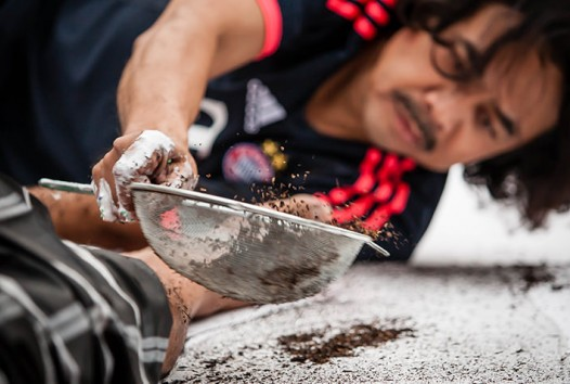 Photo of a man on the ground with a sieve creating artwork