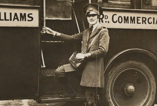 B&W photo of Neva Ferguson, a bus conductor in uniform stepping onto a bus