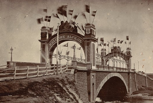Sepia photograph of stone Princes Bridge crossing the Yarra River in Melbourne decorated with flags and bunting for the 1867 visit of Alfred, Duke of Edinburgh