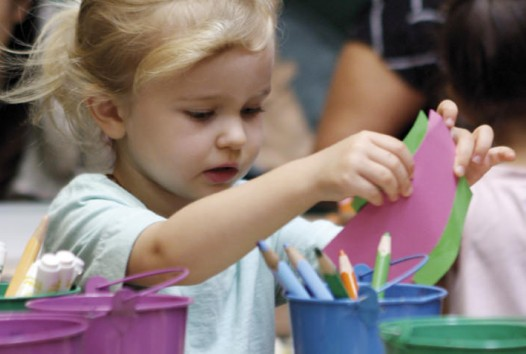 child using craft paper and pencils