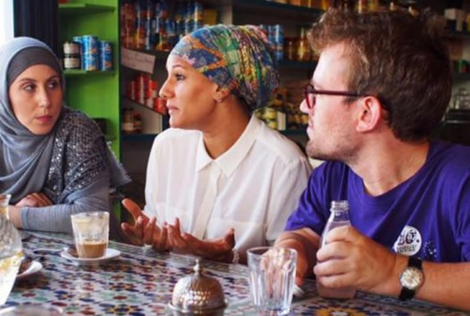 two women wearing headscarves and a man wearing a blue T-shirt sitting at a cafe table