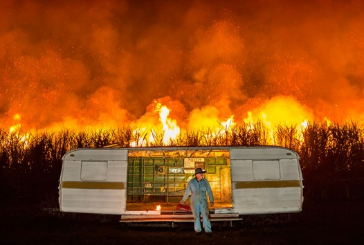 Colour photograph of bushfire behind a white caravan