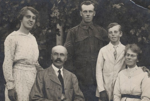 Group outdoor portrait of five people, man and woman seated, woman standing on left, man in WWI uniform standing in centre, boy standing on right