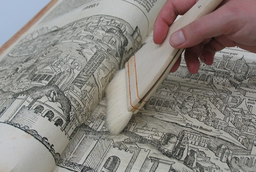 Library conservation brush a book