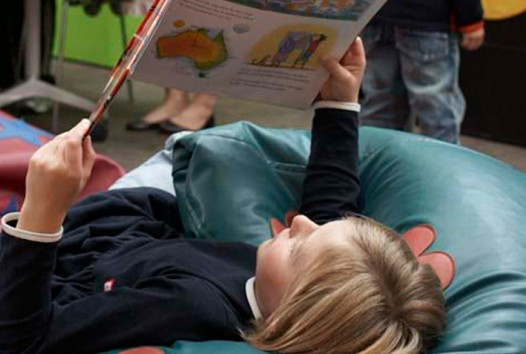 Child reading a book in a bean bag