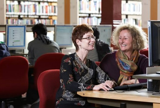 Colour photo of two women using a computer in the Redmond Barry Reading Room, State Library Victoria
