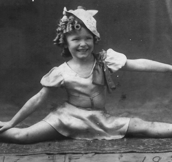 B&W photo of a little girl with ringleted hair and a big smile doing the splits