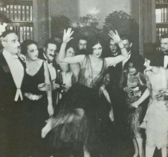 Black and white photograph of a high society party featuring a lady centre dancing
