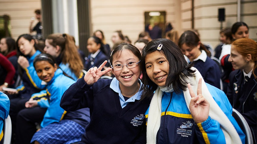 Two girls in school uniform smile and throw peace signs with fingers