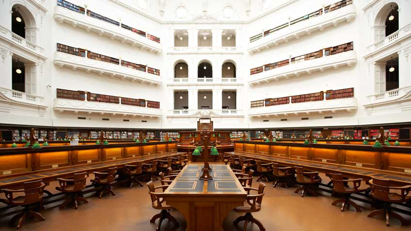 Heritage wooden desks and chairs in the La Trobe Reading Room